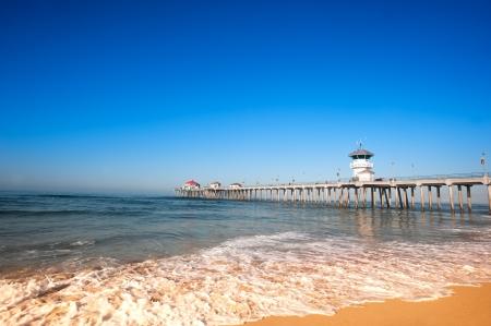 panorama beach: Huntington Beach Pier durante la mattina presto mostra le maree cambiano con spuma correre risalendo la costa.