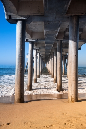 underneath: A view underneath a pier showing the pilings that support this massive structure. Stock Photo