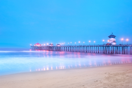 An early morning image of a pier in Huntington Beach, California using long shutter speeds to get motion blur on the water and a big blue sky.
