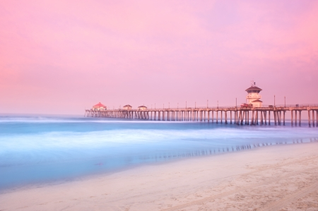 orange county: An early morning sunrise over a pier shows the ppink cloud and light cover while using a slow shutter speed to capture water movement.