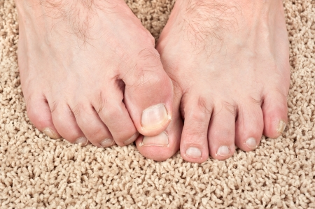 A man with itchy feet uses his big toe to scratch his other foot. Good for grooming inferences as well.