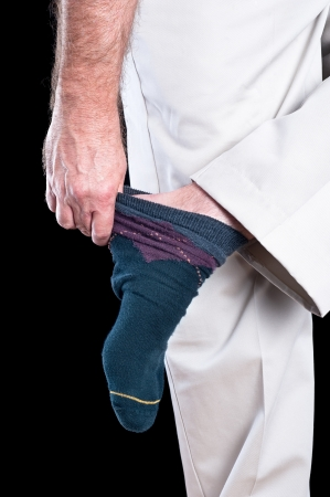 knees bent: A man removing his socks shows several inferences regarding dexterity and daily tasks adults conduct.