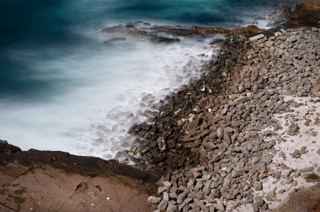 A moody, dark image of a rugged shore using slow motion effects in the camera to capture dramatic imagry of moving water and its interaction with the shoreline. photo