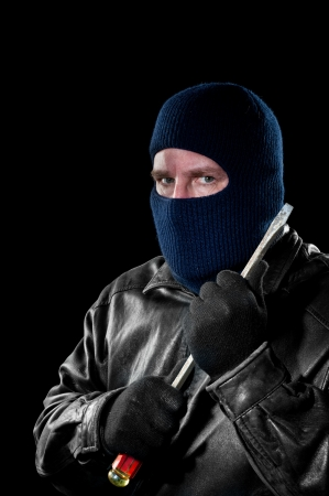 A criminal thief in a ski mask to hide his identity holds a large screwdriver as he prepared to commit a crime. photo