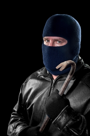 A thief wearing a ski mask to hide his identity holds a crowbar and prepares to commit a crime. Stock Photo - 16037318