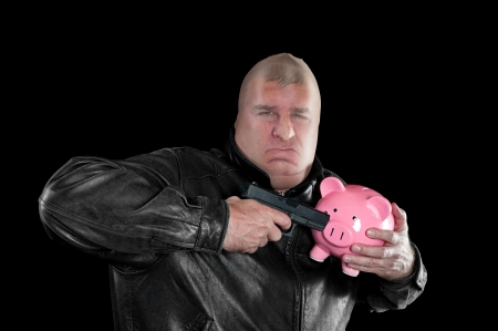 A masked thief threatening to shoot a piggy bank as he steals it during a bad economy. Stock Photo - 16037316