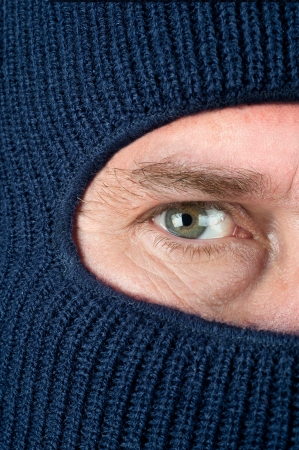 ski mask: A close up of a burglar peering through a blue ski mask to hide his identity.