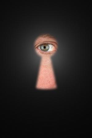 Creepy man peeking through a keyhole with focus on his eyeball. 스톡 콘텐츠