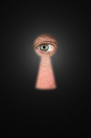 Creepy man peeking through a keyhole with focus on his eyeball. Stock Photo