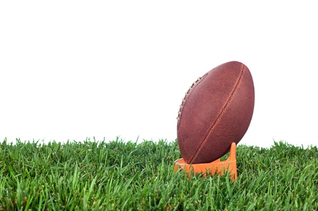 kick off: Football tee on green grass waiting for a kick off. White background for placement of copy. Stock Photo