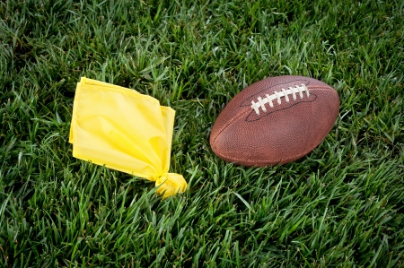 penalty flag: A yellow penalty flag and football lie motionless on a playing field. Stock Photo