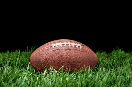 A pigskin football lying in the grass against a black background for placement of copy.