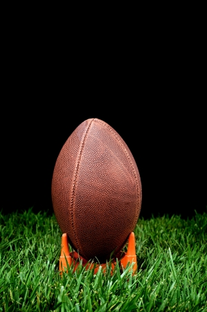 kickoff: A football kickoff on a grass field with a black background to represent nighttime.