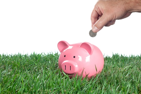 A man places a quarter into his piggy bank to save for the future. Stock fotó