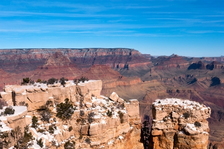 vastness: A giant ledge covered with snow at the Grand Canyon in Arizona