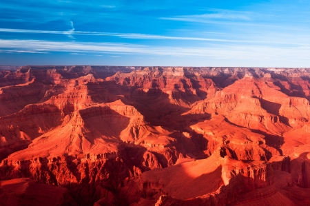 A deep orange sunset at the Grand Canyon turns the mountains a vibrant orange. photo