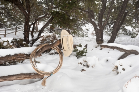 ranching: Western ranching equipment including a lasso and cowboy hat on a fence in the thick winter snow. Stock Photo