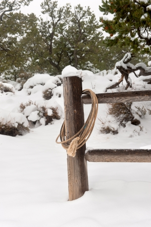 A wrangler lasso draped over a fence post in a snowy, remote rural setting Stock Photo - 17179671