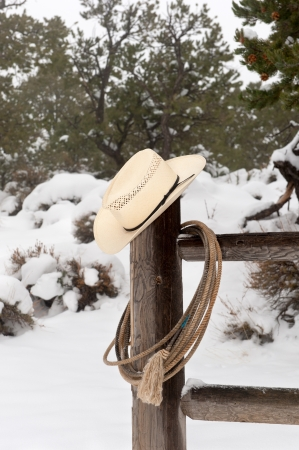 A cowboy's wrangler hat and lasso hanging on a corral fence post in a snowy, mountain ranch. Stock Photo - 17179661