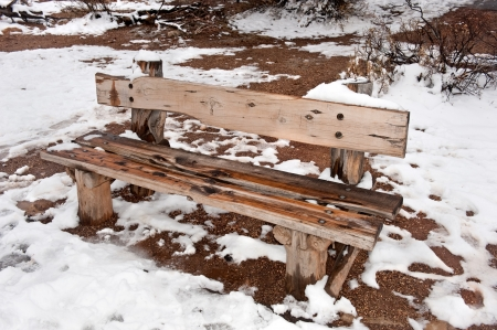 winder: A wet and cold wooden park bench during a snowy winder day.