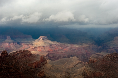 A moody image of the Grand Canyon National Park in Arizona during a cloudy day in which a spark of light peeked through the clouds to gently light part of the mountains.