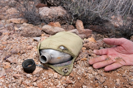 A hiker in the extreme wilderness succumbs to dehydration while in the remote desert, indicated by an old, empty canteen. Stockfoto