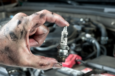 An auto mechanic holds an old, dirty sparkplug over a car engine he is tuning up.