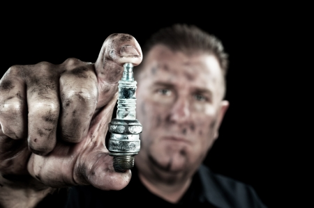 An automechanic shows a damaged and worn sparkplug as he performs a tune up.