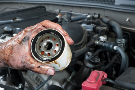 An auto mechanic shows an old, dirty oil filter just removed from a car during general maintenance Foto de archivo