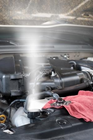 A car's overheated raiator shoots out hot steam.