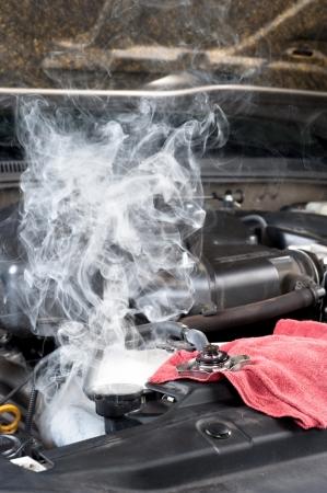 An overheated car engine smokies as the radiator cools down.