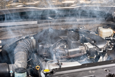 A smokey car engine shows signs of a lack of maintenance. Foto de archivo