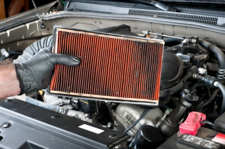An auto mechanic wearing protective work gloves holds a dirty, clogged air filter over a car engine during general auto maintenance.  Stockfoto