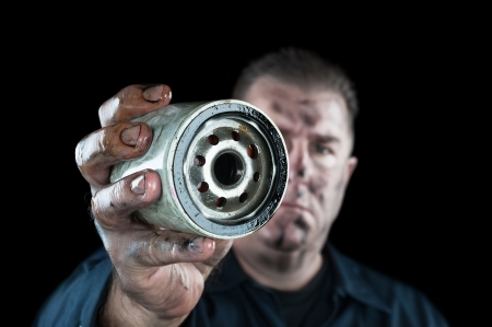 An auto mechanic showing a dirty oil filter during general car maintenance