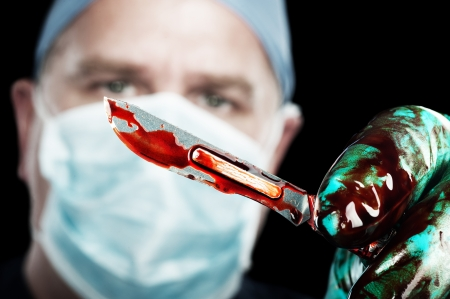 A male surgeon holds up a sharp, bloody scalpel during surgery Imagens
