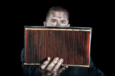 air filter: An auto mechanic holds up a filthy, grungy air filter removed from a car during normal maintenance.