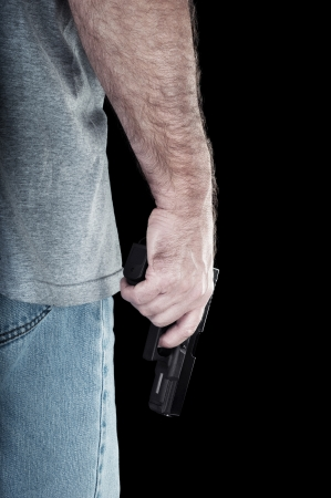 semi automatic: A man carries a semi automatic pistol looking for trouble.