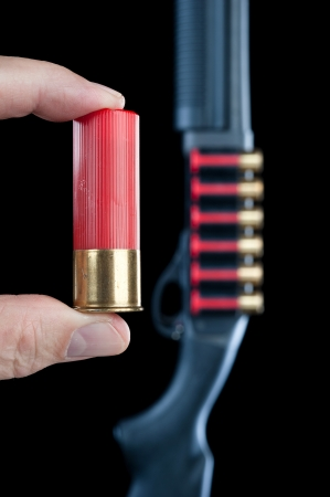 ownership and control: A man displays a shotgun shell next to a shotgun in the background. Stock Photo