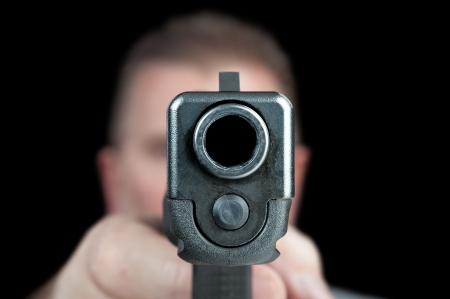 Un hombre apunta con su pistola semi automática. Selectivamente centrado en la parte delantera de la pistola.