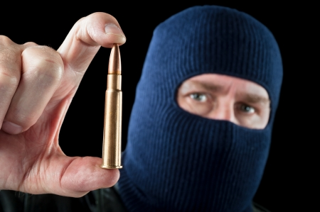 ownership and control: A terrorist wearing a ski mask as a disguise holds out a large automatic rifle bullet.