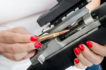 A woman with red painted fingernails loads a 223 bullet into an automatic assault rifle. photo