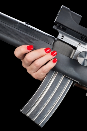 A woman with pretty red painted fingernails holds onto an assault rifle with a fully loaded magazine. photo