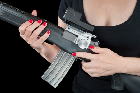 Woman with beautiful red fingernails holding a black and silver assault rifle isolated on black. photo