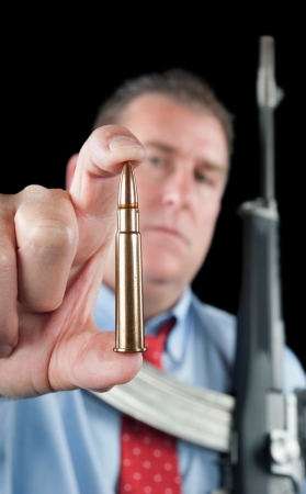 ownership and control: A businessman wearing a dress shirt and necktie shows off a large 223 bullet for his assault rifle. Stock Photo