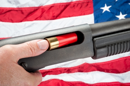 ownership and control: A man loads a shotgun shell into a pump action shotgun.  Shot against an American flag.
