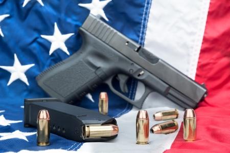 amendment: Una pistola con un cargador lleno y balas dispersas en una bandera estadounidense. Foto de archivo