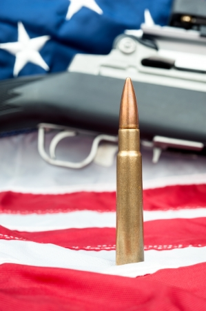 ownership and control: A single bullet in front of an assault rifle sitting on an American flag. Stock Photo