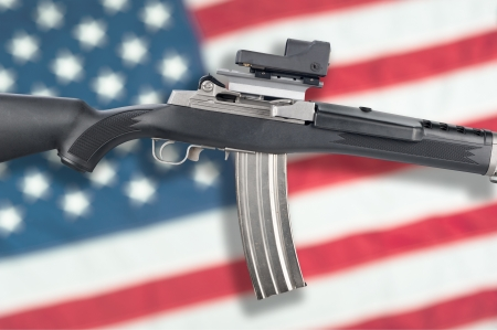 ownership and control: An assault rifle isolated over an American flag for use as gun control inferences or any other weapon scheme a designer might need. Stock Photo