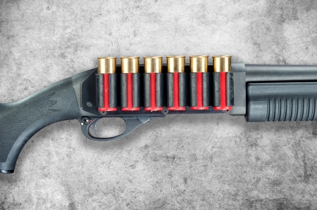 ownership and control: A shotgun with red shell cartridge ammo isolated against a grunge gray background.