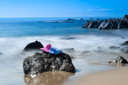 A beach goer's pink sunhat and towel rest on a rock along a beach in southern California. photo